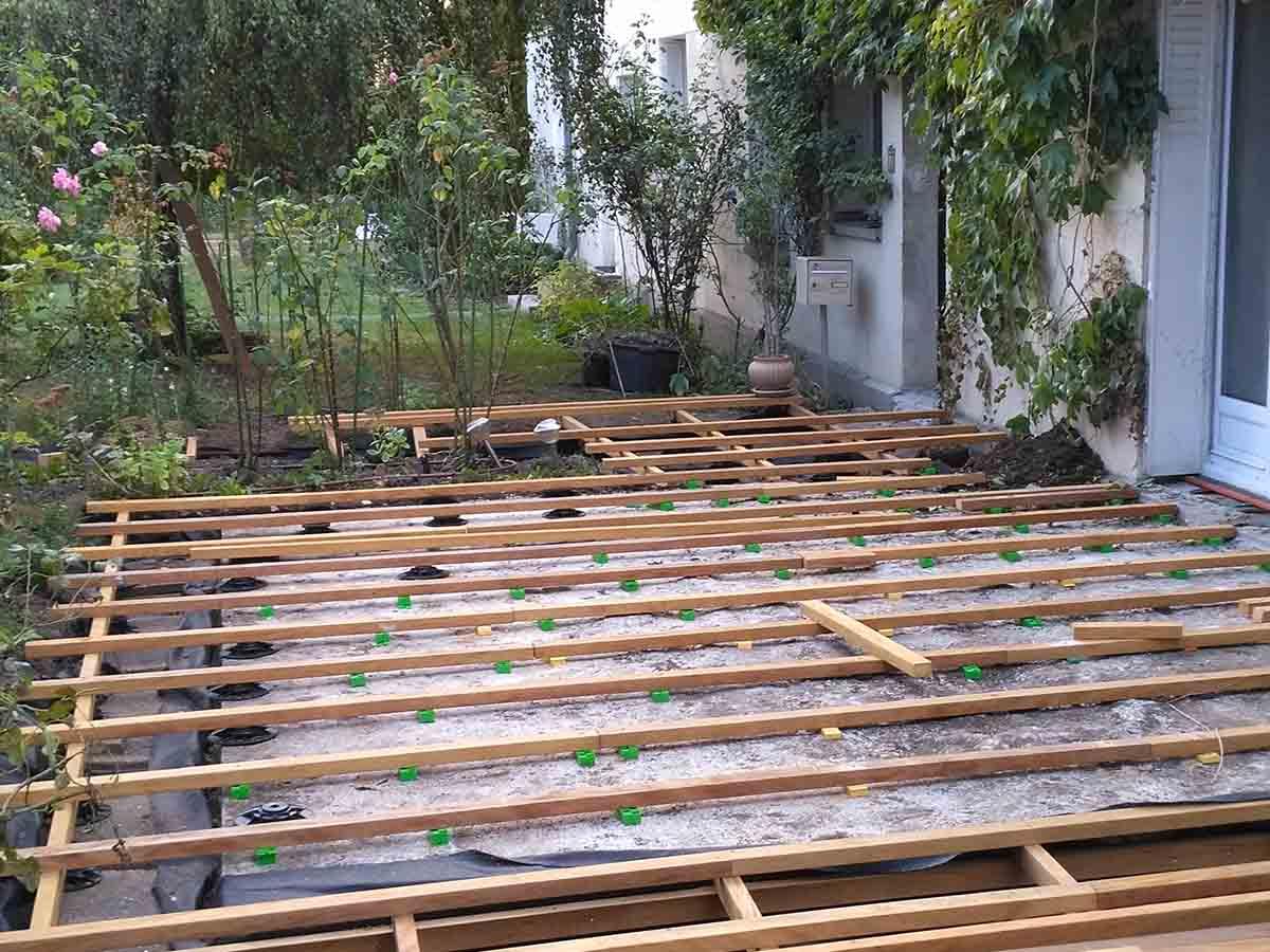 Sur les parties sur terrain naturel, on construit une double structure de lambourdes posées sur plots. Les plots sont posés sur des dalles béton pour améliorer la stabilité
