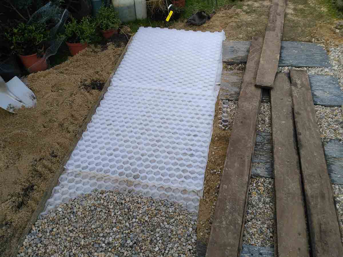 Le gravier est versé sur des dalles alvéolées qui vont rendre l'allée beaucoup plus stable.